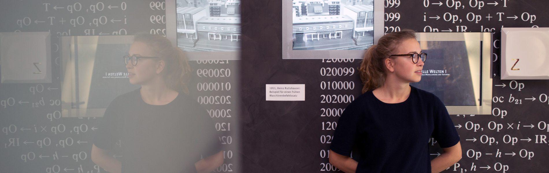 Eine Person steht vor einer dunklen Wand mit mathematischen Formeln. Dahinter eine Zeichnung von Gebäuden.