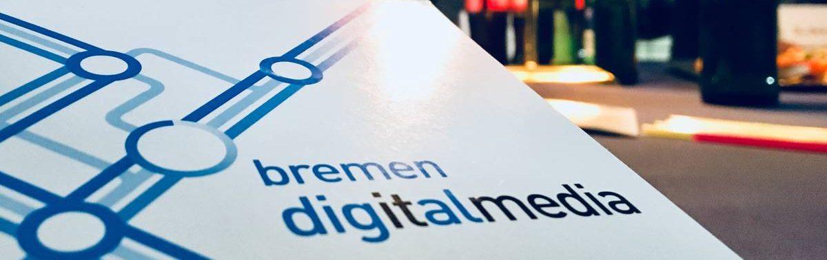 """Im verschwommenen Hintergrund kann man vier Personen erkennen. Im Fokus steht das Logo von """"bremen digitalmedia""""."""