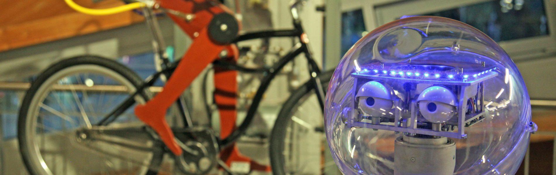 Dieses Bild zeigt den Kopf eines Roboters und Roboterbeine auf einem Fahrrad bei der langen Nacht der Museen.