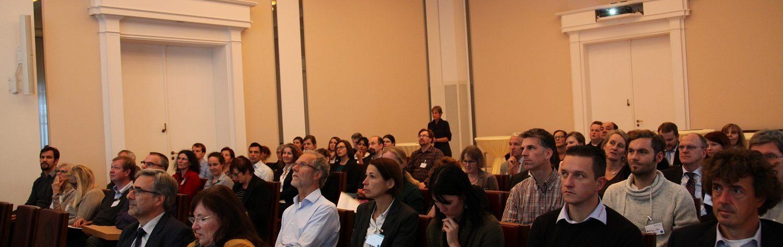 Dieses Foto zeigt diverse Menschen von vorne, die einem Vortrag zuhören.