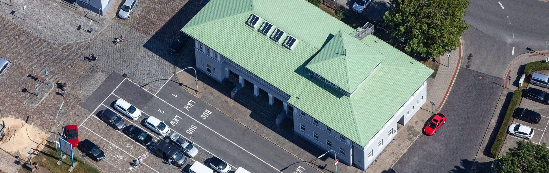 Auf diesem Bild ist das Fährhaus Bremerhaven zu sehen. Es hat ein helles, minzgrünes Dach, das sehr auffällig ist.