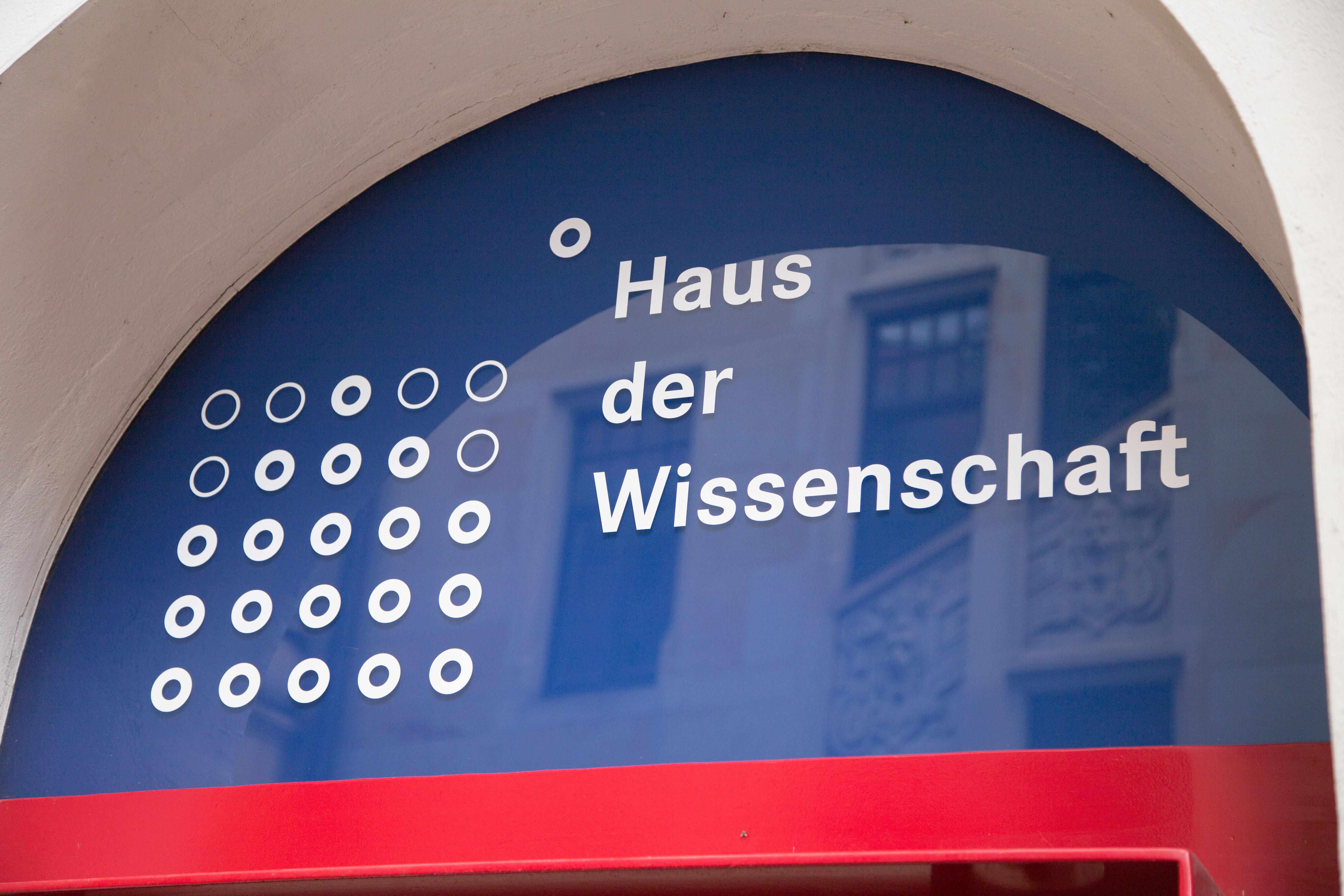 Auf diesem Bild ist das Logo des Hauses der Wissenschaft über dem Eingangsbereich zu sehen.