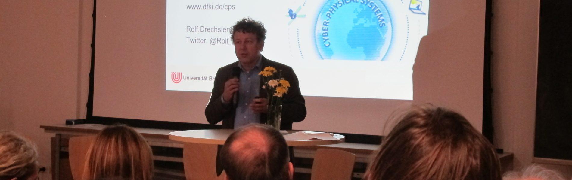 """Auf dem Bild sieht man wie Professor Doktor Rolf Drechsler einen Vortrag über """"Digitalisierung, virtuelle Welten, künstliche Intelligenz - wie wird sich unsere Arbeit und unser Leben verändern"""" im Fährhaus Bremerhaven hält."""
