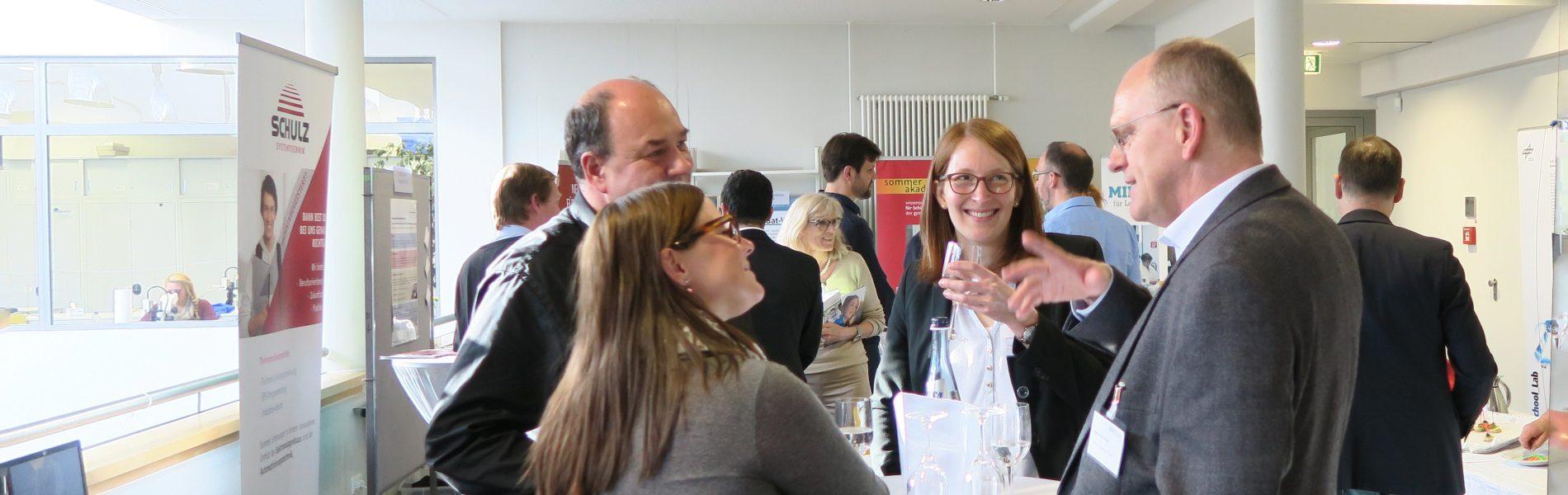 Dieses Bild zeigt vier Menschen an einem Stehtisch, die lachend diskutieren.