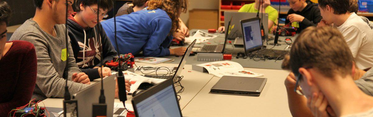 In der nordbord Programmierwerkstatt sitzen zehn Jugendliche an Laptops. Sie verkabeln kleine Autos.