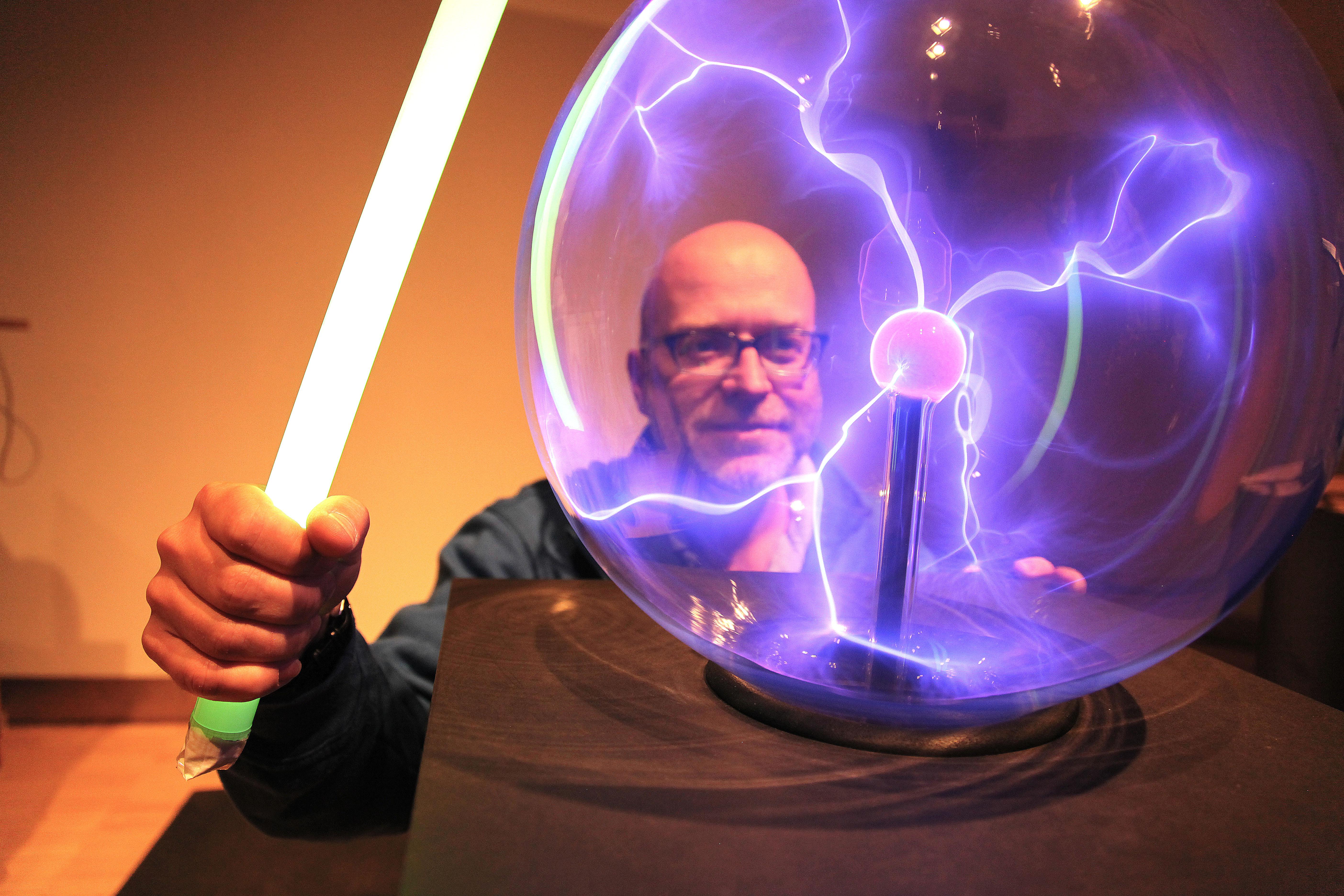 Das Bild zeigt einen Mann vor einer Plasmakugel. Die gläserne Kugel ist von der Mitte zum Rand mit kleinen, lilanen Blitzen durchzogen.