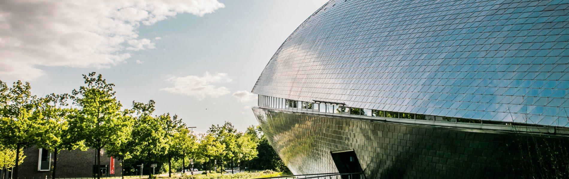 Das Foto zeigt das Universum Bremen bei Tag. Das Gebäude reflektiert Bäume und den Wolkenhimmel.