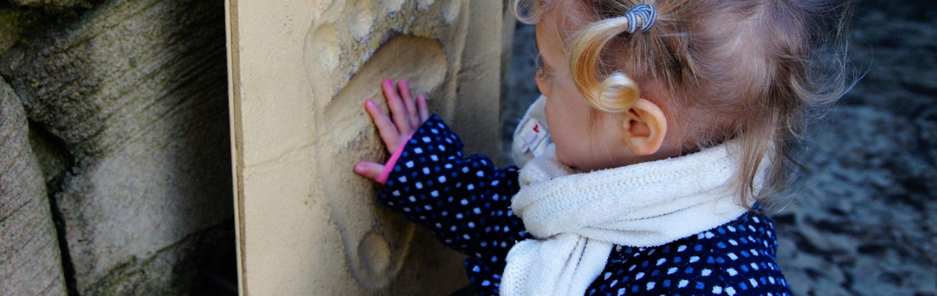 Das Bild zeigt ein Kind, das seine Hand in den Fußabdruck eines Eisbären legt. Die Pfote des Eisbären ist weitaus größer, als die Hand des Kindes.