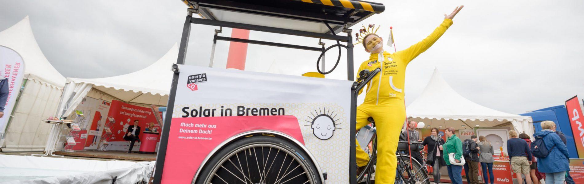 """Das Bild zeigt die Solarfrau Sunna, die komplett in gelb gekleidet ist. Sie fährt auf einem Dreirad mit dem Schriftzug der Kampagne """"Solar in Bremen""""."""